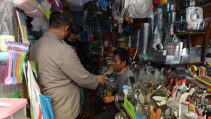 Petugas membagikan masker kepada warga di Pasar Jatinegara, Kamis (10/9/2020). Pembagian masker serta himbauan memakai masker saat keluar rumah dan ditempat Himb ini dilakukan untuk pencegahan penularan Covid-19 dimana kasus Covid-19 terus meningkat. (merdeka.com/Imam Buhori)