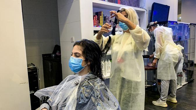 Seorang penata rambut mengenakan masker memotong rambut pelanggannya di sebuah pusat kecantikan wanita di Riyadh, Arab Saudi (21/6/2020). Pemerintah Arab Saudi mulai membuka kembali kegiatan perekonomian setelah melonggarkan lockdown Covid-19. (AFP Photo/Rania Sanjar)