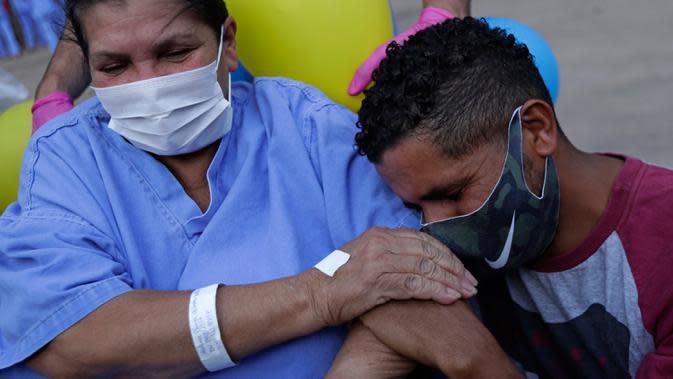 Helena Elvira (63) menerima pelukan dari putranya saat keluar dari rumah sakit di Stadion Nasional Mane Garrincha di Brasilia, Brasil, Kamis (15/10/2020). Rumah sakita darurat tersebut memulangkan tiga pasien COVID-19 terakhir setelah dinyatakan sembuh (AP Photo/Eraldo Peres)