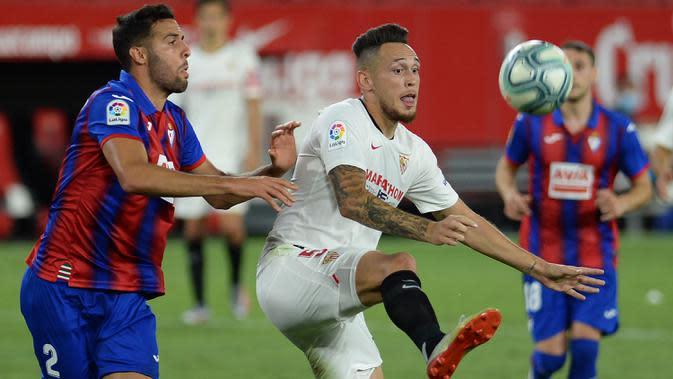 Gelandang Sevilla, Lucas Ocampos, berebut bola dengan bek Eibar, Esteban Burgos, pada laga lanjutan La Liga pekan ke-34 di Estadio Ramon Sanchez Pizjuan, Selasa (7/7/2020) dini hari WIB. Sevilla menang 1-0 atas Eibar. (AFP/Cristina Quicler)