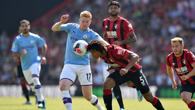 Gelandang Manchester City, Kevin De Bruyne, berebut bola dengan bek Bournemouth, Nathan Ake, pada laga Premier League 2019 di Stadion Vitality, Minggu (25/8). Manchester City menang 3-1 atas Bournemouth. (AFP/Glyn Kirk)