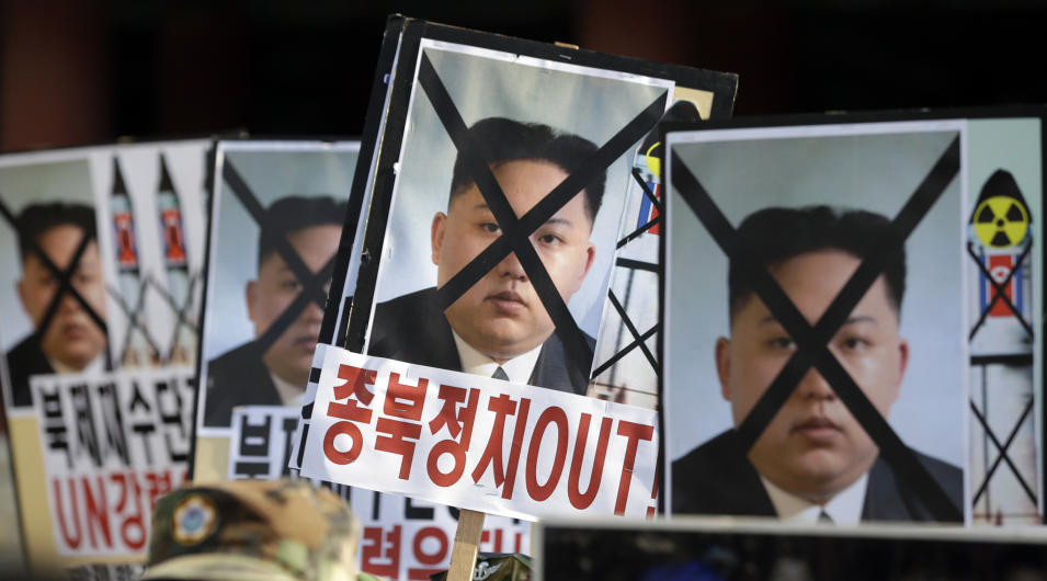 "South Korean protesters hold the pictures of North Korean leader Kim Jong Un during a rally denouncing North Korea's rocket launch in Seoul, South Korea, Wednesday, Dec. 12, 2012. North Korea successfully fired a long-range rocket on Wednesday, defying international warnings as the regime of Kim Jong Un took a giant step forward in its quest to develop the technology to deliver a nuclear warhead. The letters read ""Out, Pro-North Korea politic."" (AP Photo/Lee Jin-man)"