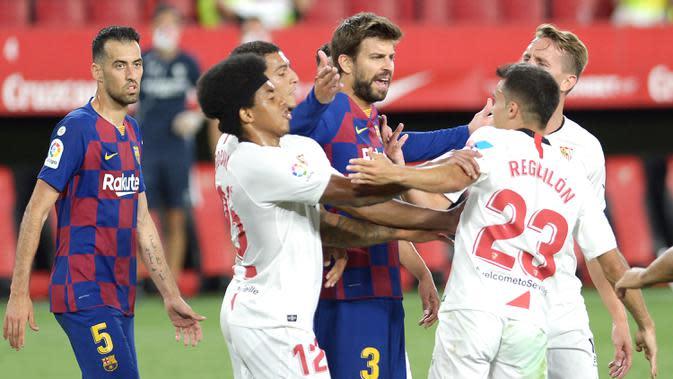 Bek Barcelona, Gerard Pique, bersitegang dengan bek Sevilla, Sergio Reguilon, dalam laga lanjutan La Liga Spanyol, Sabtu (20/6/2020) dini hari WIB. Barcelona bermain imbang 0-0 atas Sevilla. (AFP/Cristina Quicler)