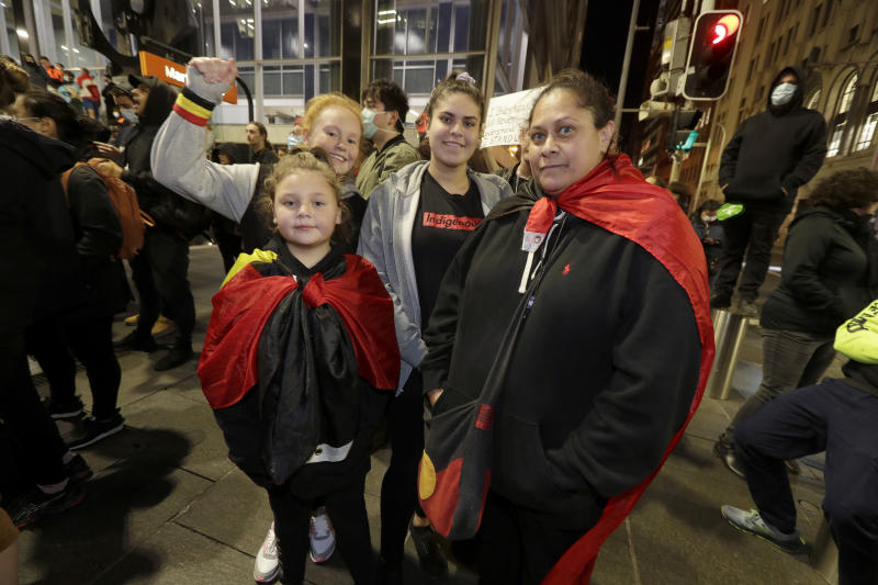 Amanda Hill, right, attends a protest with family members in Sydney, Tuesday, June 2, 2020, to support the cause of U.S. protests over the death of George Floyd and urged their own governments to address racism and police violence. Floyd died last week after he was pinned to the pavement by a white police officer who put his knee on the handcuffed black man's neck until he stopped breathing. (AP Photo/Rick Rycroft)