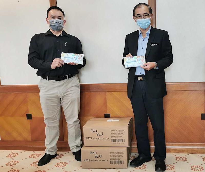 BZU BZU's regional sales director Edmund Chin (left) and deputy Education Minister Datuk Mah Hang Soon (right) with the face masks for students. — Picture courtesy of BZUBZU Malaysia