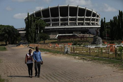 A couple walk near Nigeria's National Theatre in Lagos, Nigeria, on Wednesday, April 3, 2013. Nigeria's iconic National Theatre, long in disrepair, is now at the center of a massive redevelopment plan that could be worth millions of dollars. Nigeria's federal government has plans to use money leasing the swampy land in Lagos around the theater to private investors so they can build a mall, a five-star hotel and other amenities. However, some have doubts that the project will actually raise money for the theater. Meanwhile, the plans have already likely encouraged local officials to demolish the homes of slum dwellers living around the theater. (AP Photo/Sunday Alamba)