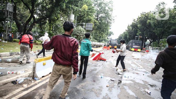 Bentrokan antara pengunjuk rasa tolak UU Cipta Kerja dan aparat kepolisian pecah di kawasan Patung Kuda, Jakarta Pusat, Selasa (13/10/2020). Massa berupaya menerobos barikade polisi yang menutup akses mengarah ke Istana Kepresidenan. (Liputan6.com/Faizal Fanani)