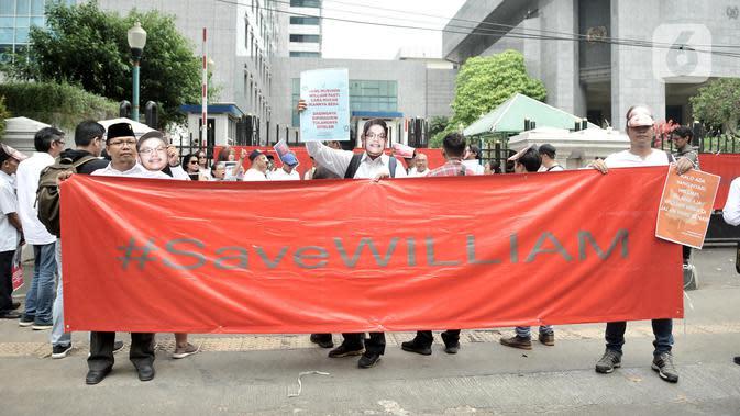 Massa Aliansi Masyarakat Untuk Transparansi mengenakan topeng William Aditya dan membentangkan poster saat aksi damai di Gedung DPRD DKI Jakarta, Rabu (4/12/2019). Mereka menuntut Badan Kehormatan DPRD Jakarta menghormati serta mendukung anggota DPRD dari fraksi PSI itu (merdeka.com/Iqbal S Nugroho)