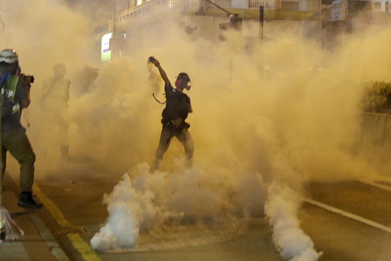 A protester throws back a tear gas canister during a confrontation with police in Hong Kong on Saturday, Aug. 3, 2019. Hong Kong protesters removed a Chinese national flag from its pole and flung it into the city's iconic Victoria Harbour on Saturday, and police later fired tear gas at demonstrators after some of them vandalized a police station. (AP Photo/Vincent Thian)