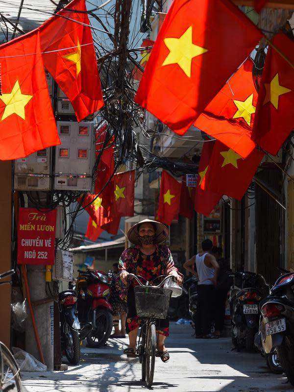 Seorang wanita mengendarai sepeda di sepanjang gang yang didekorasi dengan bendera nasional Vietnam menjelang perayaan Hari Nasional Vietnam di Hanoi (1/9/2020). Peringatan 75 tahun Hari Nasional Vietnam jatuh pada tanggal 2 September 2020. (AFP Photo/Nhac Nguyen)
