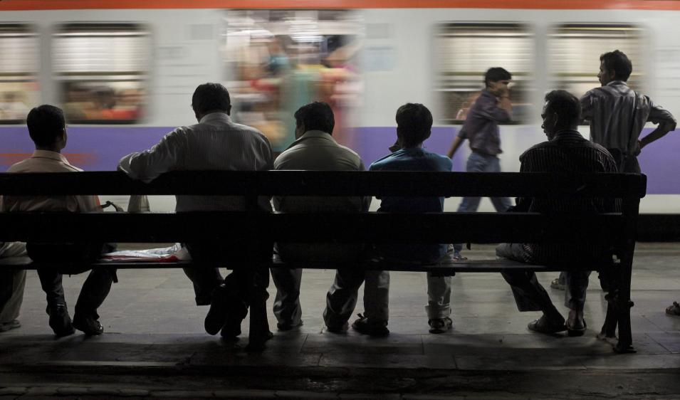 Commuters wait on the platform as a train passes by at a suburban station in Mumbai
