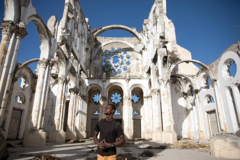 Paul Christandro poses for a picture inside of Notre Dame de l'Assomption Cathedral (Our Lady of the Assumption), destroyed in 2010 earthquake, in Port-au-Prince