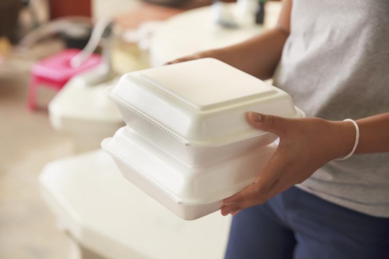 man holding styrofoam boxes