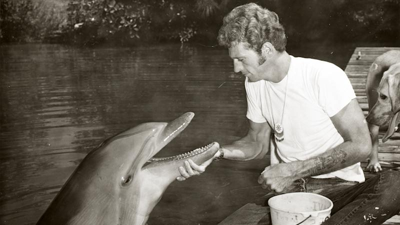 A black and white photo shows a young Ric O'Barry holding the chin of Flipper the dolphin.