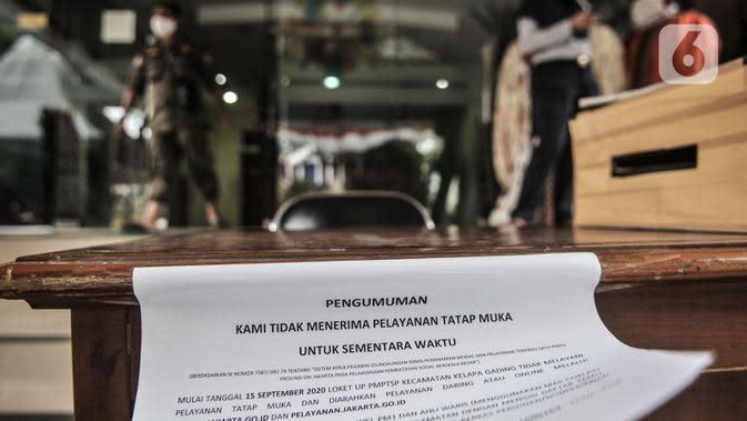 Petugas berada di dekat selebaran info ditiadakannya pelayanan tatap muka di depan Kantor Kecamatan Kelapa Gading, Jakarta, Senin (21/9/2020). Kantor Kecamatan Kelapa Gading ditutup hingga Rabu (23/9), pasca meninggalnya Camat Kelapa Gading, M Harmawan akibat COVID-19. (merdeka.com/Iqbal Nugroho)