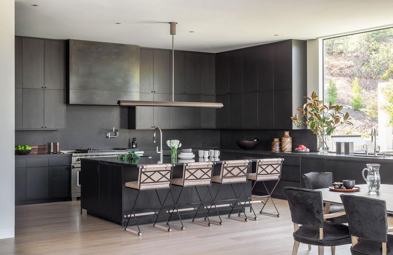 """<p>This kitchen designed by Heather Hilliard strikes the perfect balance between timeless and modern. Here, the smooth all-black surfaces are classic yet fresh and the metallic hood adds an unexpected edge. <a href=""""https://www.housebeautiful.com/room-decorating/kitchens/g1566/best-kitchen-paint-colors/"""" target=""""_blank""""></a></p>"""