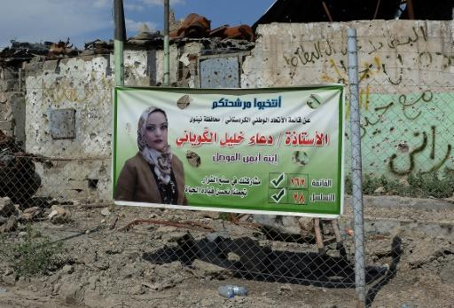 An election campaign poster is seen near a destroyed building in the devastated Iraqi city of Mosul on May 1, 2018 ahead of the upcoming parliamentary elections