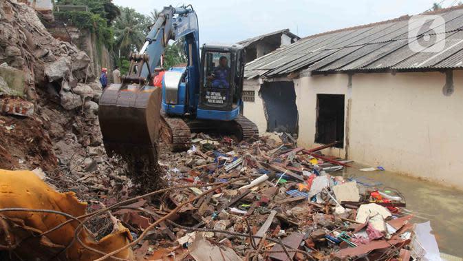 Petugas Suku Dinas Sumber Daya Air Jakarta Selatan menggunakan alat berat untuk mengeruk material pascalongsor di kawasan Ciganjur, Senin (12/10/2020). Alat berat dikerahkan mengeruk puing-puing bangunan tembok yang roboh pada kejadian longsor pada Sabtu 10 Oktober malam. (merdeka.com/Arie Basuki)