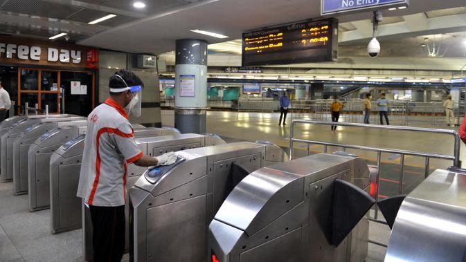 Seorang staf mendisinfeksi gerbang masuk stasiun kereta metro di New Delhi, India, 7 September 2020. Layanan kereta metro kembali beroperasi pada 7 September 2020 pagi di berbagai kota seluruh India setelah ditutup selama lebih dari lima bulan. (Xinhua/Partha Sarkar)
