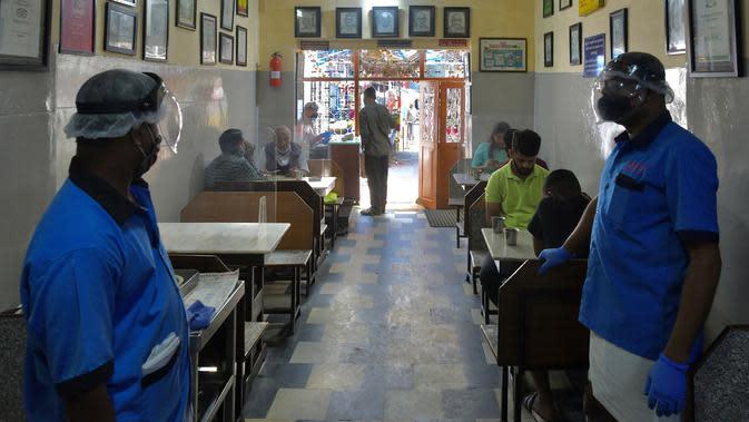 Pramusaji mengenakan pelindung wajah dan masker di sebuah restoran yang dibuka kembali usai pelonggaran lockdown di Bangalore, India, Senin (8/6/2020). Untuk keamanan pelanggan, restoran-restoran menyiapkan panel transparan di meja makan sebagai pencegahan COVID-19. (Manjunath Kiran/AFP)