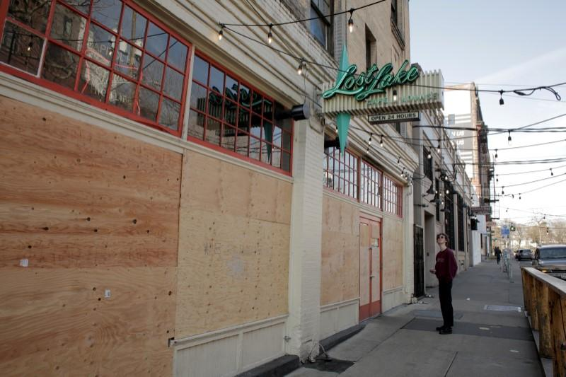 A delivery driver waits for a takeout order near the boarded up windows and doors of Lost Lake Cafe and Lounge, as authorities prohibit all dining inside restaurants during the coronavirus disease (COVID-19) outbreak, in Seattle