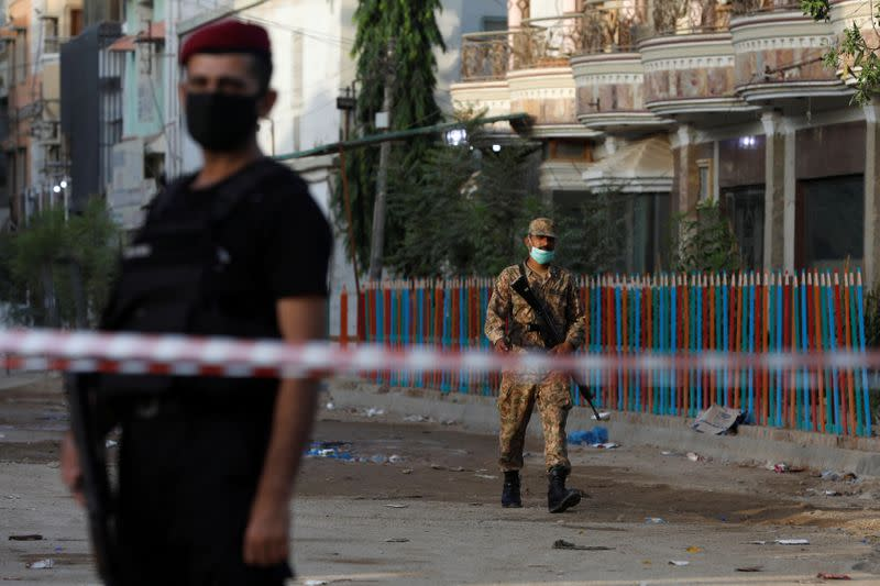 Army soldier walks along a cordoned-off street leading to the site of a passenger plane crash in a residential area near an airport in Karachi,