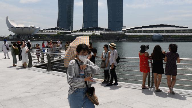 Seorang pengunjung, yang mengenakan masker pelindung di tengah kekhawatiran tentang penyebaran Virus Corona COVID-19, berjalan di sepanjang Merlion Park di Singapura pada 17 Februari 2020. (Roslan RAHMAN / AFP)