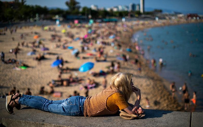 A woman smokes lying on a wall as people enjoy the beach in Barcelona - Emilio Morenatti/AP