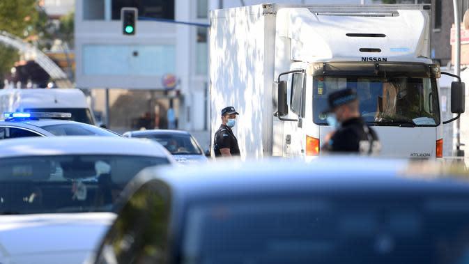 Petugas polisi setempat mengontrol pergerakan orang di sebuah pos pemeriksaan lalu lintas di kota Fuenlabrada yang tertutup sebagian, di wilayah Madrid (22/9/2020). Penguncian dilakukan akibat infeksi virus melonjak. (AFP/Oscar Del Pozo)