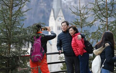 Tourists take photos in the town center on January 16, 2019 in Hallstatt, Austria. Hallstatt, known for its picturesque beauty and its location at the base of a mountain on Hallstatter See lake, is struggling to cope with large influxes of tourists throughout the year. - Credit: Getty/Andreas Gebert