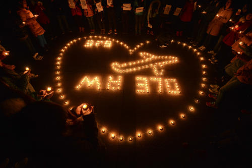 In this Thursday March 13, 2014 photo, university students hold a candlelight vigil for passengers on the missing Malaysia Airlines Flight MH370 in Yangzhou, in eastern China's Jiangsu province. China on Friday urged Malaysia's government to release any information it has regarding the missing Malaysia Airlines jetliner to help narrow the search area. (AP Photo) CHINA OUT