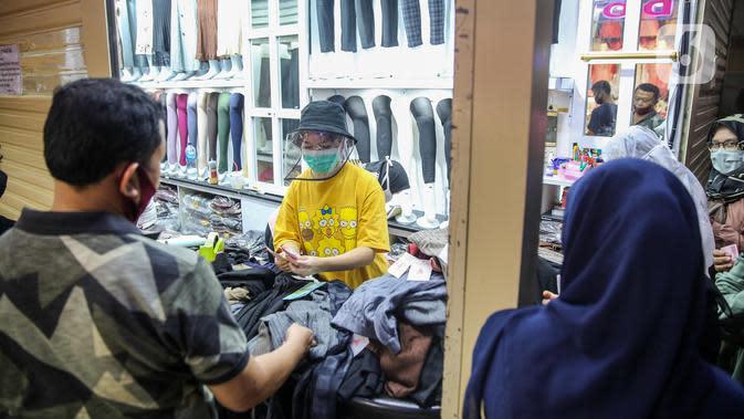 Pedagang melayani pembeli pakaian di salah satu kios Pasar Tanah Abang Blok A, Jakarta, Senin (15/6/2020). Setelah hampir tiga bulan ditutup, kawasan Pasar Tanah Abang kembali beroperasi pada Senin (15/6) diikuti dengan penerapan protokol kesehatan pencegahan Covid-19. (Liputan6.com/Faizal Fanani)