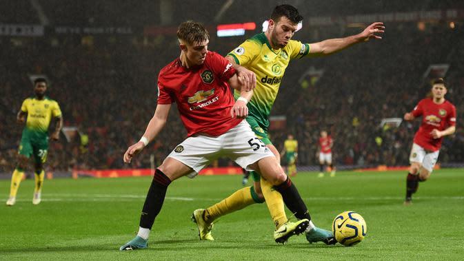 Bek Norwich City, Grant Hanley (kanan) berebut bola dengan bek Manchester United, Brandon Williams (kiri) selama pertandingan pertandingan lanjutan Liga Inggris di Old Trafford (11/1/2020). MU menang telak 4-0 atas Norwich. (AFP/Oli Scarff)