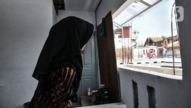 Wiwiek saat menyaksikan pekerja yang sedang membangun gedung sekolah tepat di depan rumahnya di Jalan Cempaka Baru I, RT 015/003, Kemayoran, Jakarta, Senin (31/8/2020). Pembangunan itu menutup akses jalur keluar masuk dan harus melewati pintu samping. (merdeka.com/Iqbal S Nugroho)