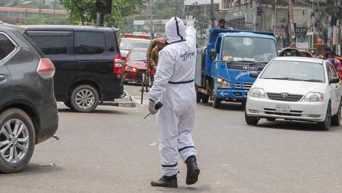 Polisi mengenakan alat pelindung diri saat mengatur lalu lintas di Dhaka, Bangladesh, Senin (11/5/2020). Jalan-jalan utama Dhaka kembali ramai sehari setelah toko-toko dan pasar kembali dibuka secara terbatas mengikuti aturan pemerintah. (Xinhua/Stringer)