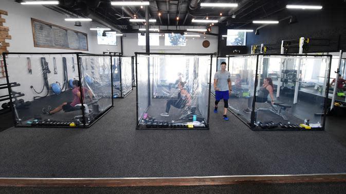 Peet Sapsin memimpin kelas dengan orang-orang berada dalam kotak plastik di Inspire South Bay Fitness di Redondo Beach, California pada 15 Juni 2020. Ruangan gym dengan plastik sebagai pemisah itu agar pengunjung dapat tetap berolahraga sambil tetap menjaga jarak fisik. (FREDERIC J. BROWN / AFP)
