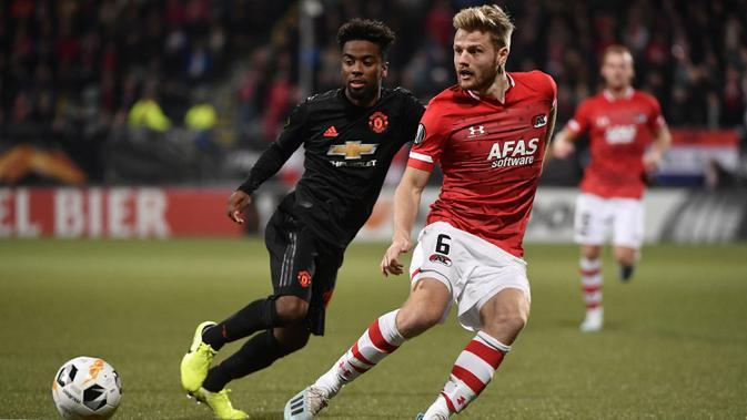 Gelandang Manchester United, Angel Gomes, menjafa pergerakan gelandang AZ Alkmaar, Fredrik Midtsjo, pada laga Liga Europa di Stadion ADO, The Hague, Kamis (3/10). Kedua klub bermain imbang 0-0. (AFP/John Thys)