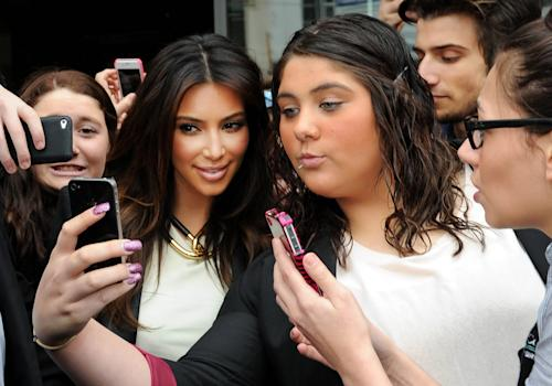 "File - In this Friday, Sept. 21, 2012 file photo Kim Kardashian, left, is surrounded by her fans who are attempting to have their photographs taken with her as she leaves a radio station in Melbourne, Australia. ""Selfie"" the smartphone self-portrait has been declared word of the year for 2013 by Britain's Oxford University Press. (AP Photo/Mal Fairclough, File)"