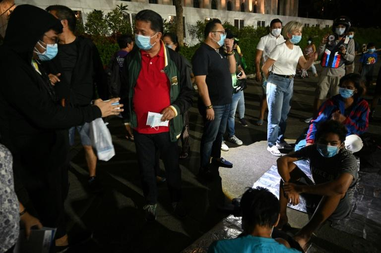 Ash from Taal volcano reached Manila, where local officials (L) talked to homeless people and distributed face masks for protection