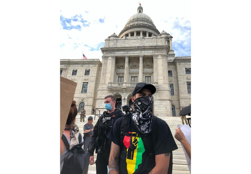 """CORRECTS NAME TO TOBY ANDERSON- Toby Anderson, 30, attends a rally in Providence, Rhode Island, on Friday, June 5, 2020. Anderson, who is biracial, said he downloaded the Signal app for encrypted communications several days earlier at the request of his mom. """"She's a black woman in America,"""" he said, and thus was worried about his safety. (AP Photo/Matt O'Brien)"""