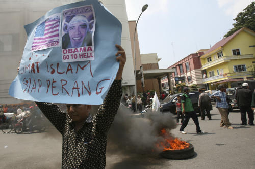 "An Indonesian Muslim holds up a poster as a tire burns during a protest against an American film that ridicules Prophet Muhammad outside the U.S. Consulate in Medan, North Sumatra, Indonesia, Tuesday, Sept. 18, 2012. Indonesians continue to protest the anti-Islam film ""Innocence of Muslims,"" torching the flag and tires outside the consulate in the country's third largest city of Medan. The poster reads: ""Muslims are ready for war.""(AP Photo/Binsar Bakkara)"