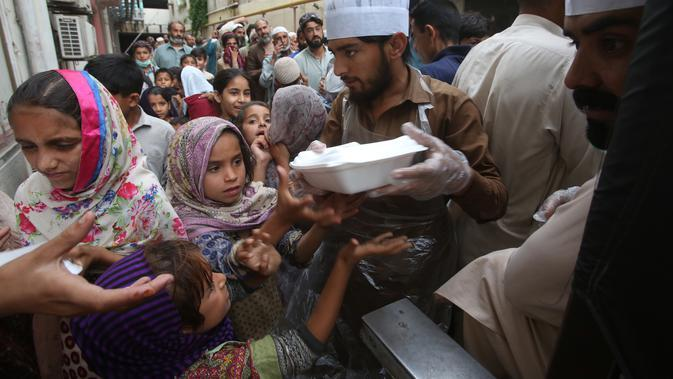Relawan mendistribusikan kotak makanan untuk orang-orang yang berbuka puasa bersama selama bulan suci Ramadan di Peshawar, Pakistan, Senin (11/5/2020). Warga berbuka puasa bersama setelah pemerintah melonggarkan lockdown terkait pandemi virus corona COVID-19. (AP Photo/ Muhammad Sajjad)