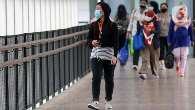 Warga menggunakan masker berjalan di JPO kawasan Jalan Jenderal Sudirman, Jakarta, Kamis (10/9/2020). Setelah mempertimbangkan sejumlah faktor, di antaranya ketersediaan tempat tidur rumah sakit, PSBB DKI Jakarta kembali diperketat per Senin (14/9). (Liputan6.com/Helmi Fithriansyah)