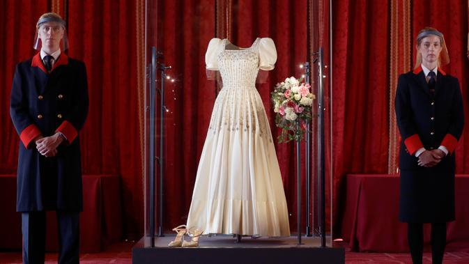 Petugas kerajaan berdiri di samping gaun pengantin Putri Beatrice yang dipajang di Kastil Windsor, Windsor, Rabu (23/9/2020). Beatrice menikah dalam balutan gaun pengantin dari era tahun 1960-an rancangan Norman Hartnell yang dipinjamkan sang nenek, Ratu Elizabeth II. (AP Photo/Kirsty Wigglesworth)