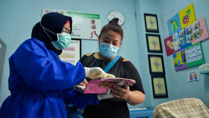 Petugas kesehatan berbincang dengan orang tua bayi setelah melakukan imunisasi anak di sebuah Pukesmas di Banda Aceh, Aceh, Senin (15/6/2020). Memasuki tatanan normal baru, pelayanan imunisasi anak kembali dibuka setelah sebelumnya sempat terhenti akibat pandemi COVID-19. (CHAIDEER MAHYUDDIN/AFP)