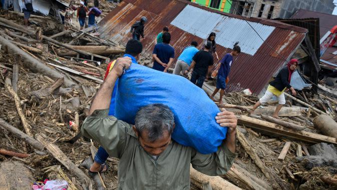 Penduduk desa mencari barang-barang dari rumah mereka sebelum mengungsi setelah banjir bandang di Kabupaten Luwu Utara, Sulawesi Selatan, Rabu (15/7/2020). Akibat banjir bandang tersebut mengakibatkan 16 orang meninggal dunia dan ratusan rumah tertimbun lumpur. (Hariandi HAFID / AFP)