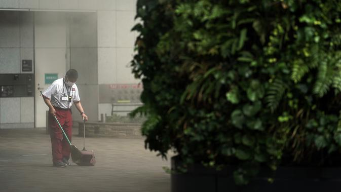 Seorang pegawai gedung yang memakai masker untuk membantu mencegah penyebaran virus corona membersihkan di dekat area kabut di Tokyo, Kamis (10/9/2020). Ibu kota Jepang itu mengonfirmasi lebih dari 270 kasus virus corona pada Kamis. (AP Photo / Eugene Hoshiko)