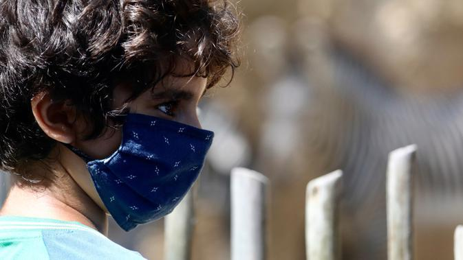 Seorang anak yang mengenakan masker mengunjungi Kebun Binatang Los Angeles, Amerika Serikat (AS), pada 26 Agustus 2020. Kebun binatang tersebut dibuka kembali untuk umum dengan menerapkan langkah-langkah pencegahan kesehatan setelah ditutup selama 166 hari akibat pandemi COVID-19. (Xinhua)