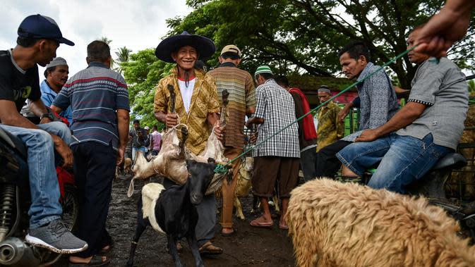 Seorang pria membawa seekor kambing di sebuah pasar yang menjual ternak menjelang perayaan Idul Fitri yang menandai berakhirnya bulan suci Ramadan di Sibreh, provinsi Aceh (20/5/2020). (AFP/Chaideer Mahyuddin)