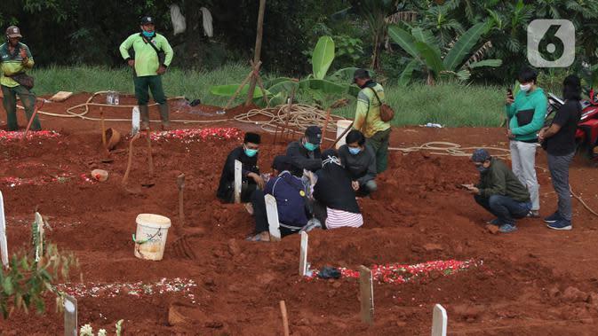 Proses pemakaman jenazah dengan menerapkan protokol Covid-19 di TPU Pondok Ranggon, Jakarta Timur, Minggu (27/9/2020). Untuk tahap kedua, Dinas Bina Marga DKI Jakarta akan membuka lahan pemakaman baru seluas 6.150 meter persegi. (Liputan6.com/Herman Zakharia)